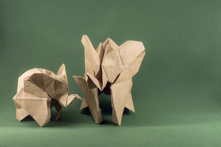 origami elephant and baby elephant made of craft paper on green background, paper and forest conservation concept, save paper save the forest, animal protect concept, mockup, copy space