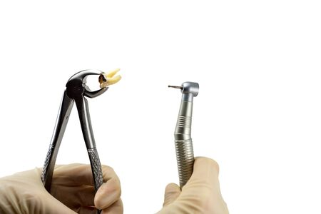 Les pinces dentaires et la pointe de la turbine dentaire décident de traiter ou d'enlever la dent isolée sur fond blanc Banque d'images