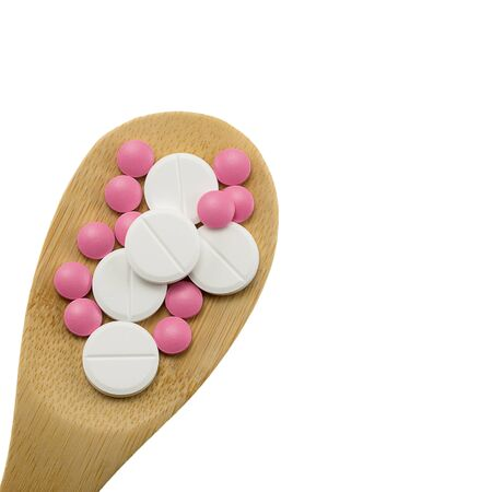 multi-colored tablets in a wooden spoon on a white background isolated, blank, mock up, copy space