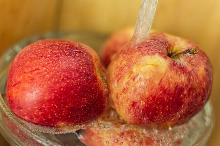 red beautiful juicy ripe apples under running water, the importance of hygiene, washing fruit before eating