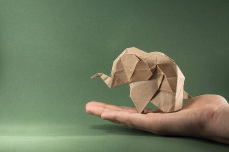 origami baby elephant made of craft paper on green background, paper and forest conservation concept, save paper save the forest, protect the animals, mockup, copy space Stock Photo