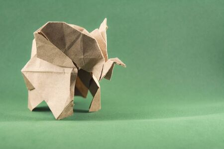 origami baby elephant made of craft paper on green background, paper and forest conservation concept, save paper save the forest, mockup, copy space
