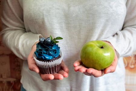 green apple and sugar cupcake in the hands, the dilemma of what to choose, the concept of healthy eating and lifestyle, the problem of diet weight loss and overweight