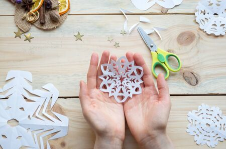 the girl makes a homemade snowflakes cut out of paper, preparation for the new year, Christmas, home decoration Foto de archivo