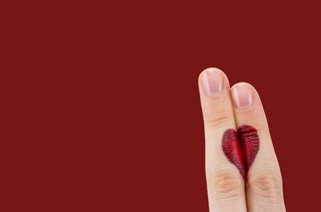 fingers coupled together with drawn heart, isolated on red background, symbol of love, relationship