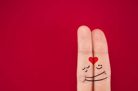 fingers coupled together with a painted heart, a cheerful smile, smileys, emojis, isolated on red background, the symbol of lbwi, relationships