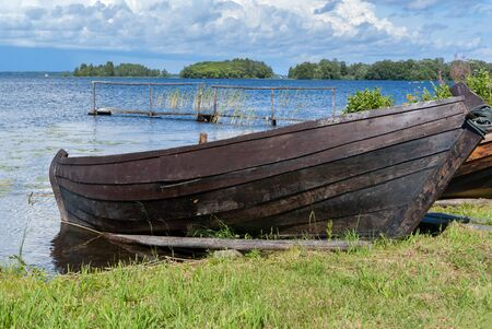 old wooden boat on oars on the shore of a blue cold lake