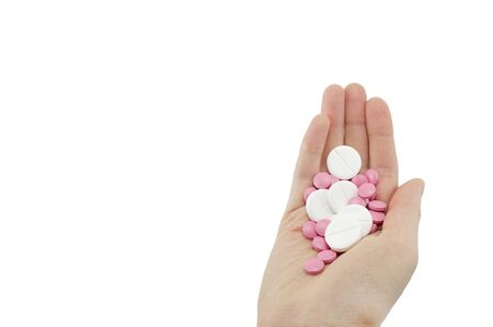 multicolored tablets of different size in hand top view close-up macro, isolated, white background
