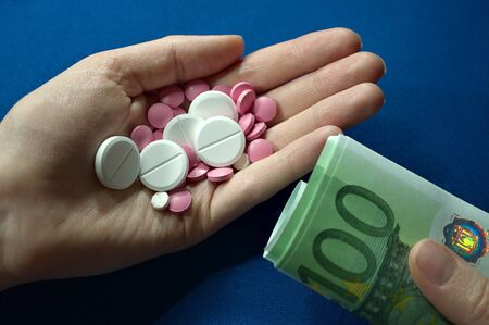 hand holding pills and hand holding money, expensive medicine, medical care not for everyone, medical insurance