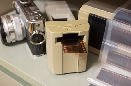 professional film scanner, vintage camera and film segments in the background, film photography, film digitization