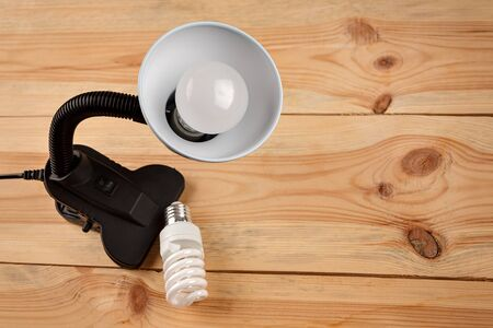 lamp with installed energy-efficient and eco-friendly led light on the background of outdated incandescent lamps and halogen lamps