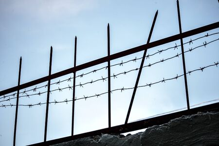 view of the fence with barbed wire against the sky, to isolation and conclusion