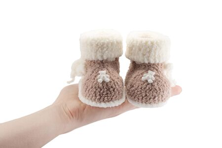 knitted baby booties for newborn on hand isolated on white background