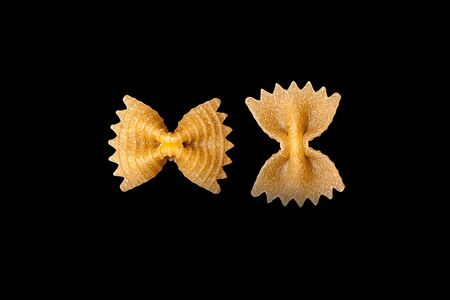 pasta from durum wheat Farfalle, bows, unprepared, raw pasta handmade on black background isolated