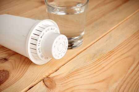 filter for cleaning tap water for drinking and a glass of filtered clean water
