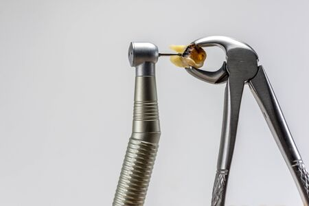 dental forceps and dental turbine tip, decide to treat or remove tooth background, dental health theme