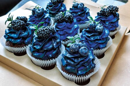 a set of beautiful mouth-watering cupcakes with blue cream and blueberries and blackberries, cakes handmade desserts, close-up