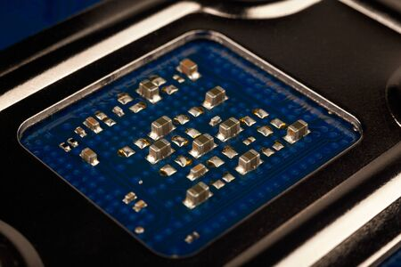 a chip in a computer with many electrical elements, a CPU, a GPU, a microchip in an electronic device, a multi-core multithreaded processor crystal, close up, macro Stock fotó