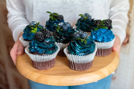 a set of beautiful mouth-watering cupcakes with blue cream and blueberries and blackberries in the hands, cakes handmade desserts, close-up Stockfoto