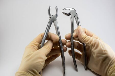dental surgical forceps to remove teeth in the hands of a dentist surgeon on a light background Reklamní fotografie