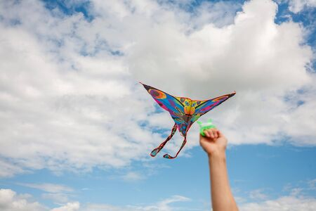 kite in hand against the blue sky in summer, flying kite launching, fun summer vacation, under the field, freedpm concept