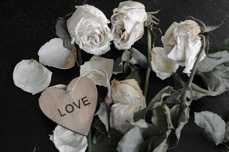 dead withered crumbling flowers roses with a wooden heart with the inscription love, as a symbol of failed love, goodbye, broken hearts, the end of relationships, divorce Stock Photo