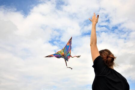 kite in hand against the blue sky in summer, flying kite launching, fun summer vacation
