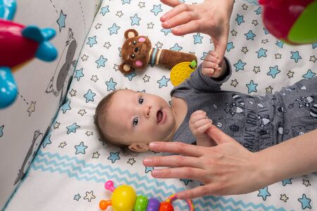 little happy motivated child is playing with dangling rattles, toys for newborn, first toy Stock Photo - 146651160