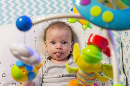 little happy motivated child is playing with dangling rattles, toys for newborn, first toy Stock Photo - 146579598