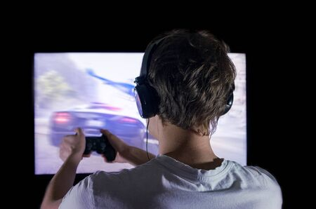 gamer with gamepad happy to win in the online game, the player with headphones in front of the monitor