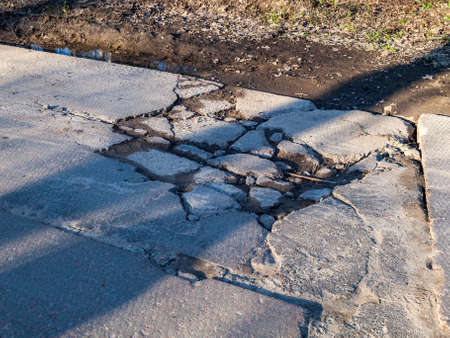 broken road with holes and protruding stones close-up, need for repair of the roadbed, cnfhst road, abandoned infrastructure