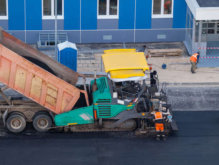 Industrial heavy road paver multifunctional modern, repair of road pavement in an urban environment, noisy work in the city 免版税图像