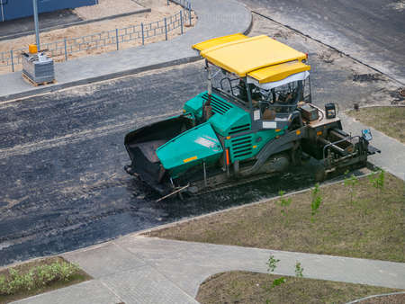 paver at the time of repairing roads, laying new roads, steamroller heavy machine, modern technology of asphalt roads and paths 免版税图像