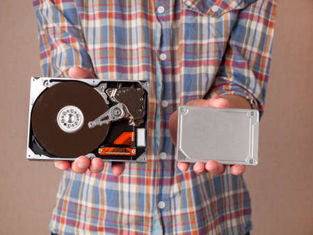 different types of computer drives, hard disk drives and SSD drives of different generations, data transfer, read and write speed, in man hands