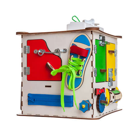 children's educational toy busycube, busyboard, isolated on a white background, the development of motor skills and coordination in kids, design, copy space