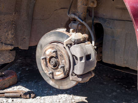 Disassembled car wheel, view of the brake caliper and disc, shock absorbers and suspension springs of the car, service and repair car