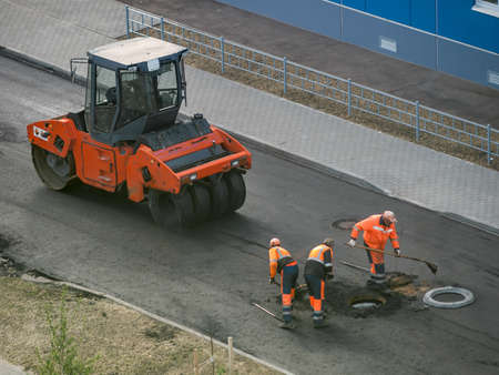 Industrial heavy roller for leveling and rolling the surface of hot asphalt, work on laying asphalt in urban areas