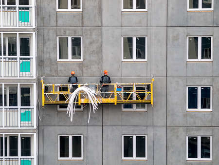 high-rise workers work on the lift in the construction of high-rise multi-storey buildings, building houses, lifting Elevator, panel construction and concrete slab reinforcement 免版税图像