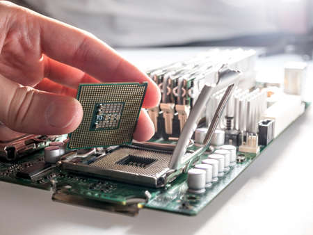 the process of connecting the CPU to the processor socket on a modern computer motherboard, replacing the silicon data processing chip, and correctly installing the central processing unit 免版税图像