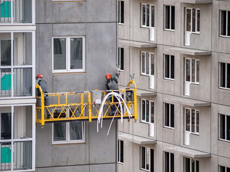 industrial climbers work on the construction of the building facade, painting the exterior of the facade of a residential building, office, high-rise multi-storey construction 免版税图像