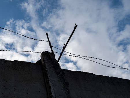 barbed wire close-up against a blue sky, the concept of incarceration, serving a sentence, restriction of freedom, isolation, crime and punishment