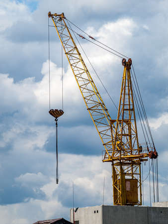 high-rise crane in the construction of high-rise buildings in the city district, against the background of the sunset