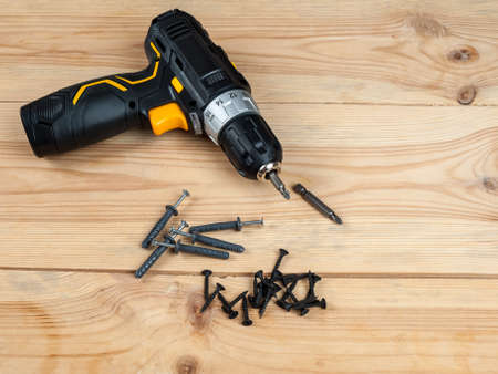 electric drill with battery, portable screwdriver for screwing screws and bolts and drilling, dowels and screws for home repairs with your own hands 免版税图像