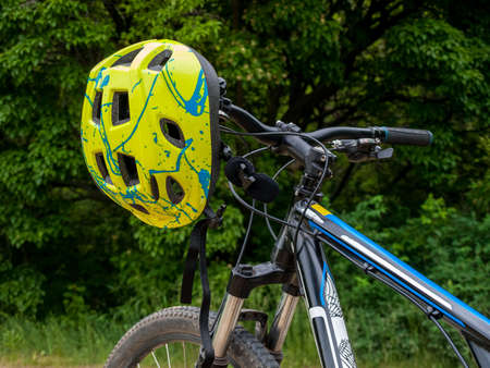 bicycle helmet hanging on the handlebar of mountain multi-speed bike, mtb, mountain bike, cycling, outdoor cycling, cycling safety 免版税图像