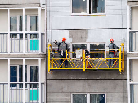 construction workers installers high-rise workers industrial climbers, painters on the lift paint the facade of the building, completion of construction of a residential building or office