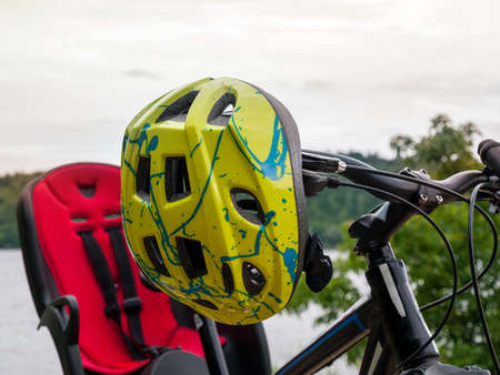 bicycle helmet hanging on the handlebar of mountain multi-speed bike, mtb, mountain bike, bicycle travel, outdoor cycling, bicycle safety with children, bicycle child safety seat 免版税图像