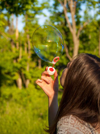 young girl inflates soap bubbles in summer in sunny weather, outdoor recreation, big soap bubbles Banco de Imagens