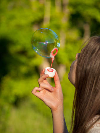 inflate big soap bubbles, girl inflates soap bubbles against the background of the sun, outdoor recreation, park in summer