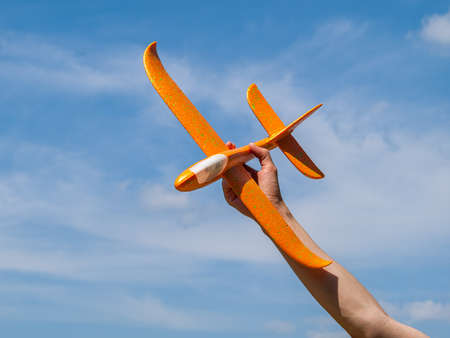 toy airplane, glider in hand against the blue clear sky in sunny summer weather, outdoor recreation