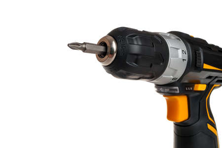 electric drill with battery, portable screwdriver for tightening screws and bolts and drilling, dowels and screws for home repairs with your own hands, selective focus on the screwdriver head, close-up